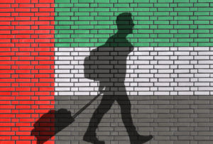 Man with suitcase and the Emirati flag illustrating moving to Dubai